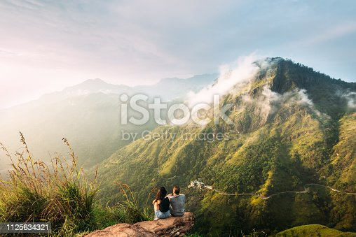 The couple greets the sunrise in the mountains. Man and woman in the mountains. Wedding travel. The couple travels around Asia. Travel to Sri Lanka. Serpentine in the mountains. People greet the dawn