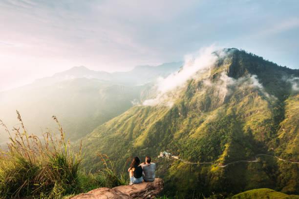 這對夫婦在山上迎接日出。山裡的男人和女人。婚禮旅行。這對夫婦在亞洲各地旅行。前往斯里蘭卡。山裡的蛇形。人們迎接黎明 - 冒險 個照片及圖片檔