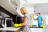 The couple is cleaning in the kitchen. Cleaning the room.