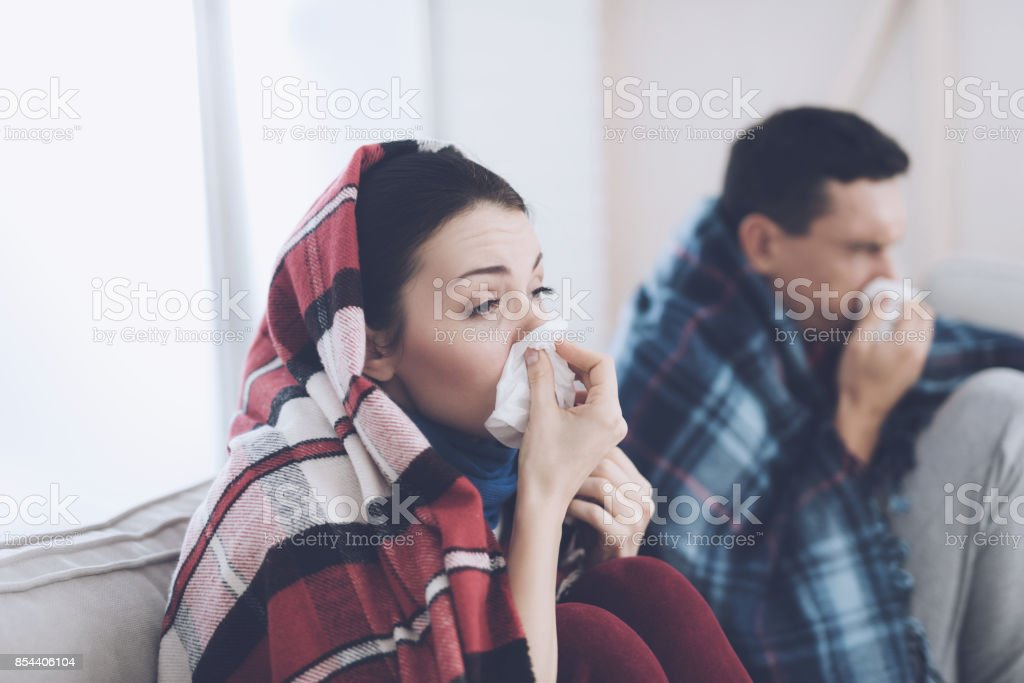 The couple is sitting on the couch wrapped in blankets. Man and woman...