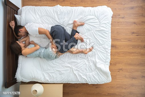 504371332 istock photo The couple laying on the bed. view from above 1077172478