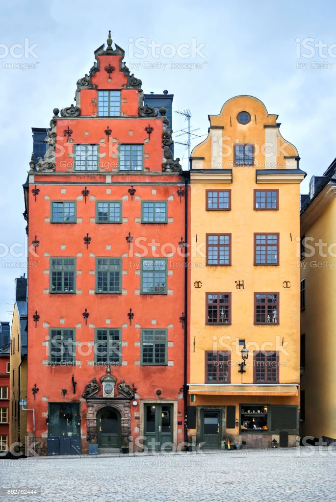 The couple of houses in the square, paved with cobblestones in the old town of Stockholm - Gamla Stan. Sweden. stock photo