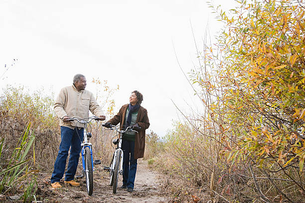 the couple pushing bicycles stock photo