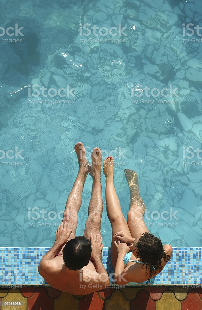 The couple sits beside water pool royalty-free stock photo