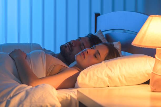 das paar im bett schlafen. nachtzeit, vollen griff fokus - nachttischleuchte touch stock-fotos und bilder