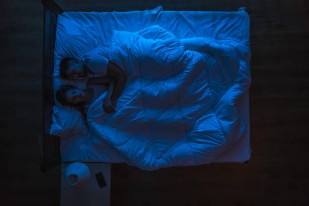 das paar schlief auf einem bett. abendliche nachtzeit. blick von oben - nachttischleuchte touch stock-fotos und bilder