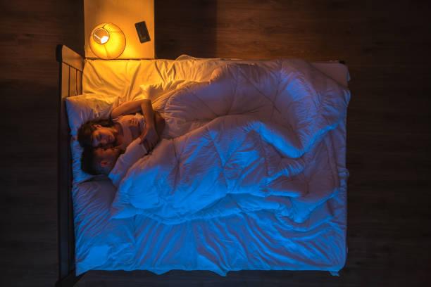 das paar schlafend auf dem bett. abendliche nachtzeit. blick von oben - nachttischleuchte stock-fotos und bilder