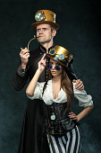 istock The couple steampunk. A man with a pipe and a girl with glasses and hat. 1019380020