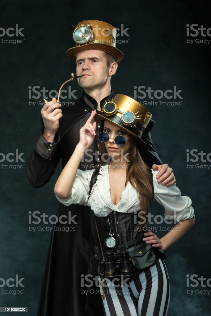 The couple steampunk. A man with a pipe and a girl with glasses and hat. stock photo