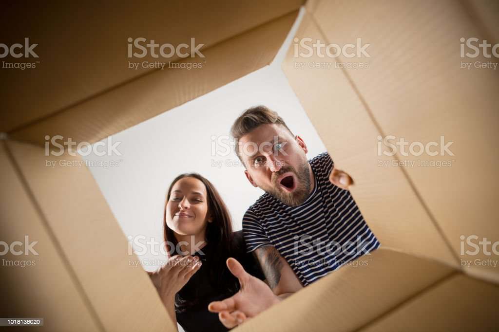 The couple unpacking and opening carton box and looking inside stock photo