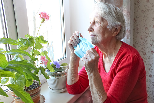 The Covid-19, health, safety and pandemic concept - senior old lonely woman wearing protective medical mask sitting near the window at home for protection from virus