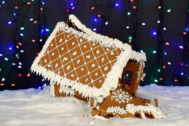Das abgestürzte handgefertigte essbare Lebkuchenhaus, Schneedekoration, Girlande Hintergrundbeleuchtung – Foto