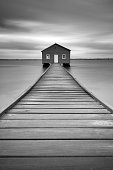 The Crawley Boatshed.  The blue boathouse on the Swan River with a wooden pier leading to the front door in Crawley, Perth, Western Australia.