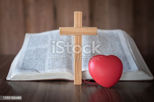 The cross and the red heart lay close together. Bible background and close-up images of the Lord Jesus' prayer Faith in the sacred power of God through prayer to Him, Christianity, Jesus.