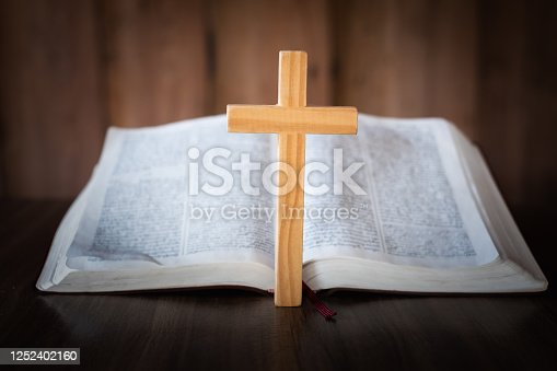 The cross was laid on the front of the Bible. The concept of prayer for the blessing of Jesus God Faith in the divine power of God through prayer to Him, Christianity, Jesus.