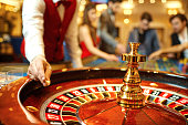 The croupier holds a roulette ball in a casino in his hand. Gambling in a casino.