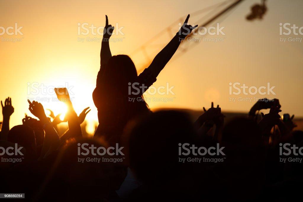 Das Publikum genießt das Sommer-Musikfestival, Sonnenuntergang, die Silhouetten Hände oben – Foto