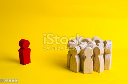 1007383644istockphoto The crowd of wooden figures of people stand distantly and look at the red man. The rejected person tries to establish contact with the group. Bad business leader, expulsion from the team. 1007383656
