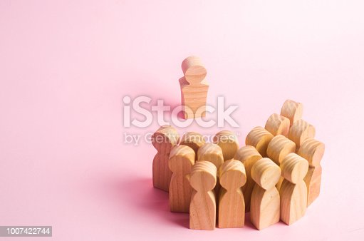 1007383644istockphoto The crowd of wooden figures of people stand distantly and look at the leader. The person tries to establish contact with the group. business leader, company management 1007422744