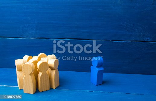 1007383644istockphoto The crowd of wooden figures of people stand distantly and look at the blue man. The person tries to establish contact with the group. Good business leader, expulsion from the team. 1048927660
