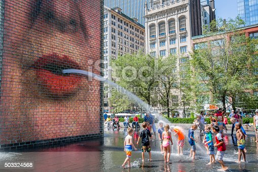 Chicago, USA - August 22, 2015:   Chidlren playing in the Crown Fountains at Millenium Park.  This animated fountain attract young and old people.  Sight in both original and refreshing, this site is very popular espacially on days of heat waves and certainely the favorite workart of children in Chicago.