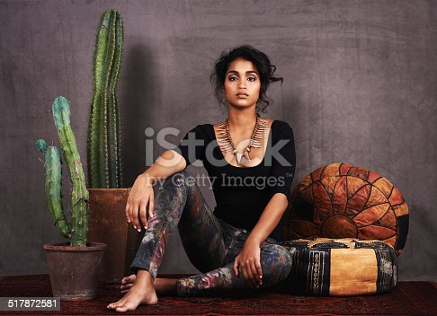 Studio portrait of a beautiful young woman sitting amongst cacti and cushions