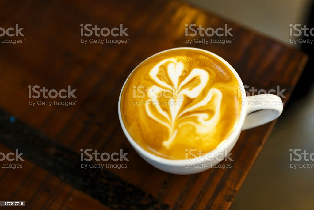 The cup hot capuchino on the wooden table background. royalty-free stock photo