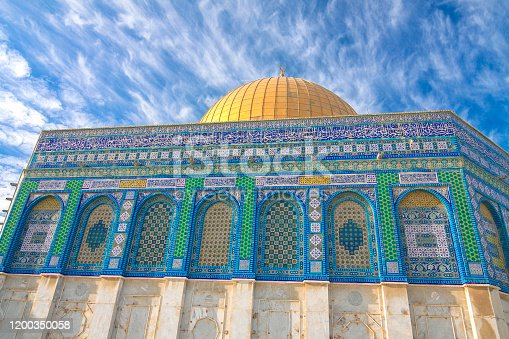 Israel - Jerusalem - Close-ip view of Dome of the Rock painted wall and golden cupola with clouds and blue sky