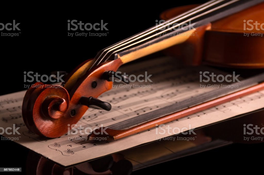 The curl of a violin and music notes isolated on black stock photo