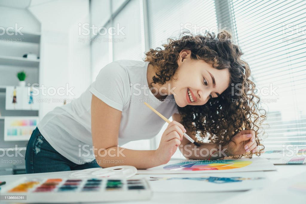The curly girl painting a picture at the table