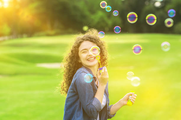 The curly woman blowing bubbles in the green park The curly woman blowing bubbles in the green park dark spots face stock pictures, royalty-free photos & images