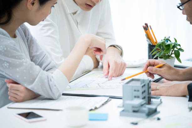 The customer and the employee are discussing the materials by looking at the materials. stock photo