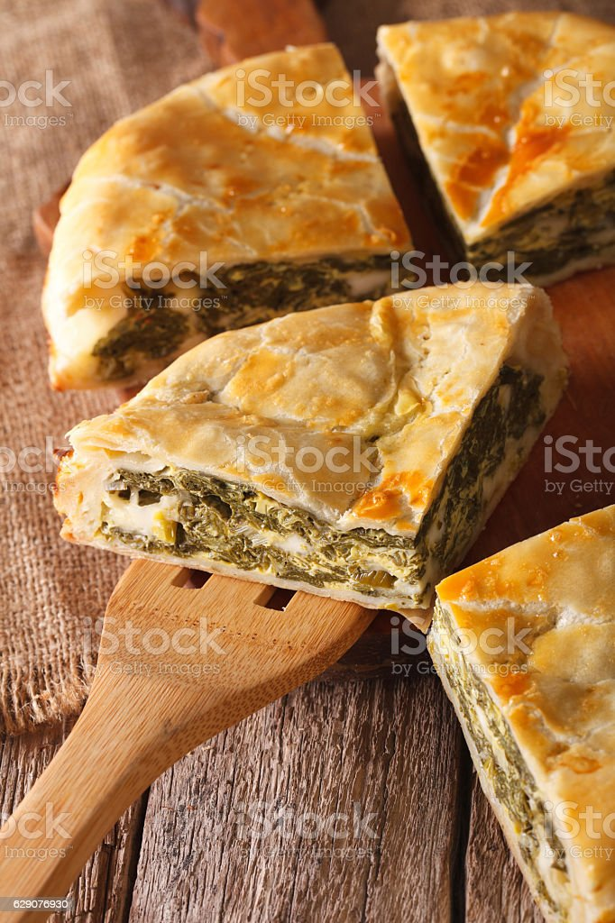 The cut pie spanakopita close-up on. vertical stock photo