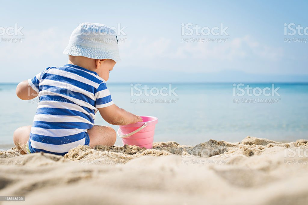 The cute baby boy playing on the beach stock photo