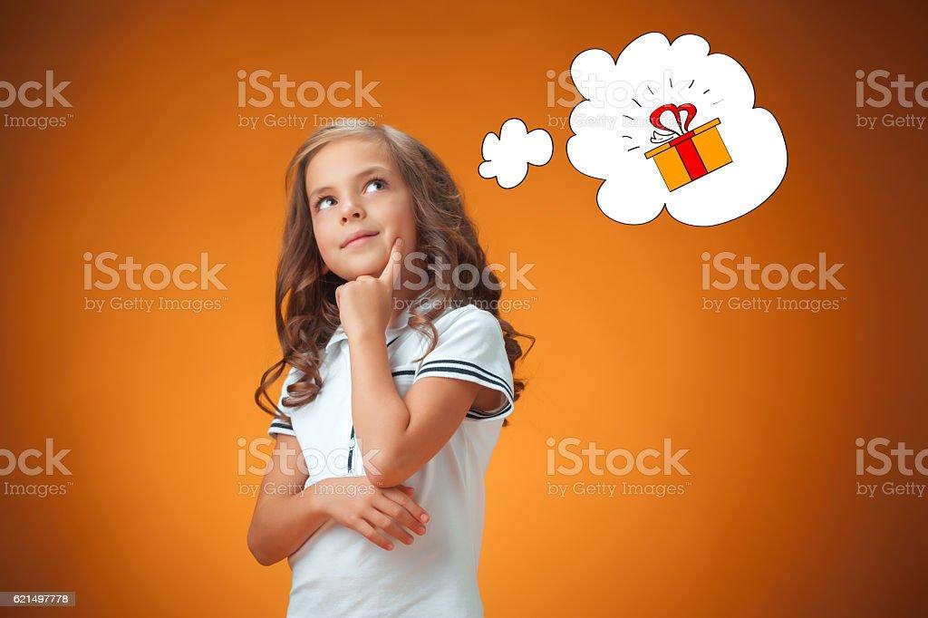 The cute thoughtful little girl on orange background Lizenzfreies stock-foto