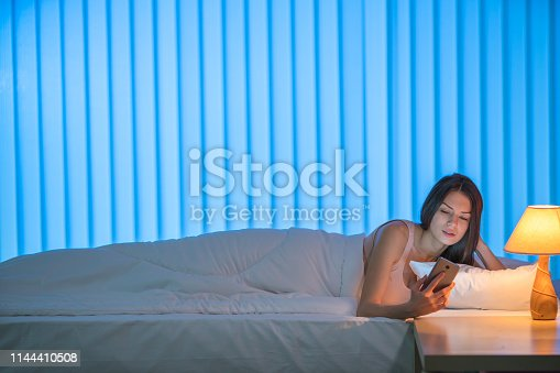 istock The cute woman lay on the bed and phone. Evening night time 1144410508