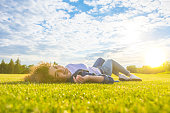The cute woman lay on the grass against the background of the sunshine