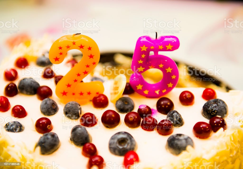 The cut-off cake with candles in figures stock photo
