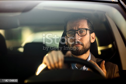 Photo of caucasian serious bearded businessman in formal wear driving car during the day.