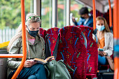 Woman sitting on a bus wearing a protective mask during the Covid 19 pandemic. She is reading a book. There are other passengers behind her who are not in focus.