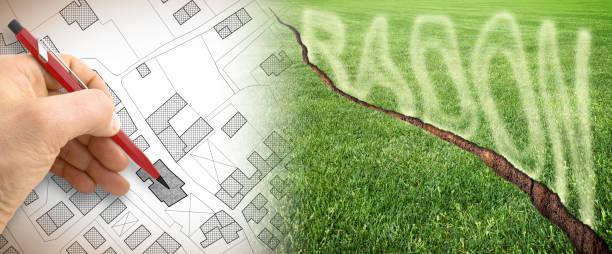 het gevaar van radongas in onze steden - concept afbeelding met gebarsten groen gemaaid gazon met radongas ontsnappen en hand opstelling over de kadastrale kaart - radon test stockfoto's en -beelden