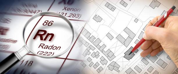 het gevaar van radongas in onze steden - concept afbeelding met periodiek systeem der elementen, vergrootglas lens en hand opstelling over de kadastrale kaart - radon test stockfoto's en -beelden
