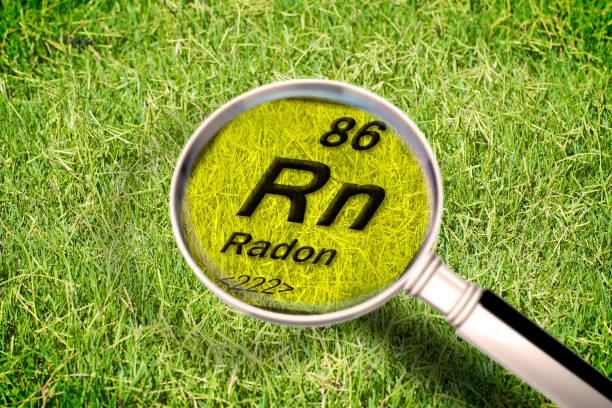 de gevaarlijke radioactieve radon gas onder de grond-conceptbeeld met periodieke tabel van de elementen, vergrotende lens en groen gras gebied op de achtergrond - radon test stockfoto's en -beelden