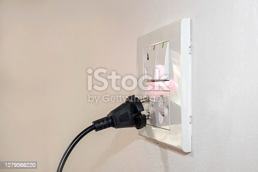 The dangers of using electricity in your home or office include a black plug that is not completely plugged into the white wall.