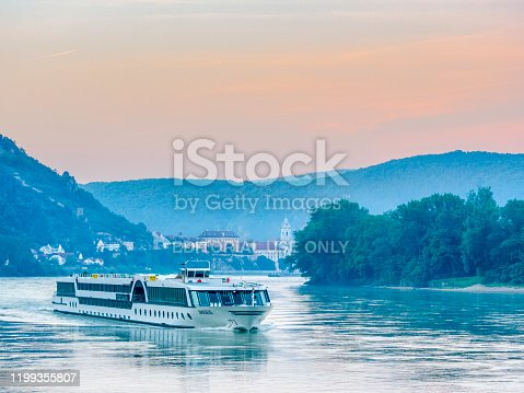The Austrian region of the Danube River Valley on May 27, 2018: View of the Danube River with the town of Durnstein and a passing river cruise boat in Austria