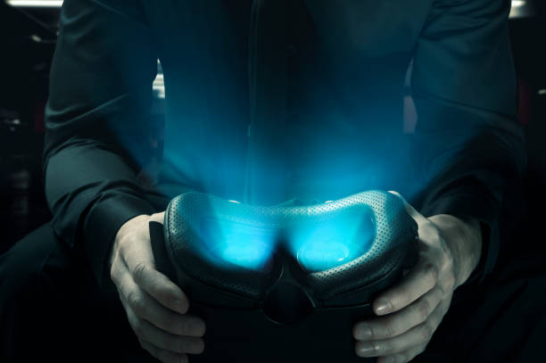 The dark side of virtual reality. Man holds glowing VR googles stock photo