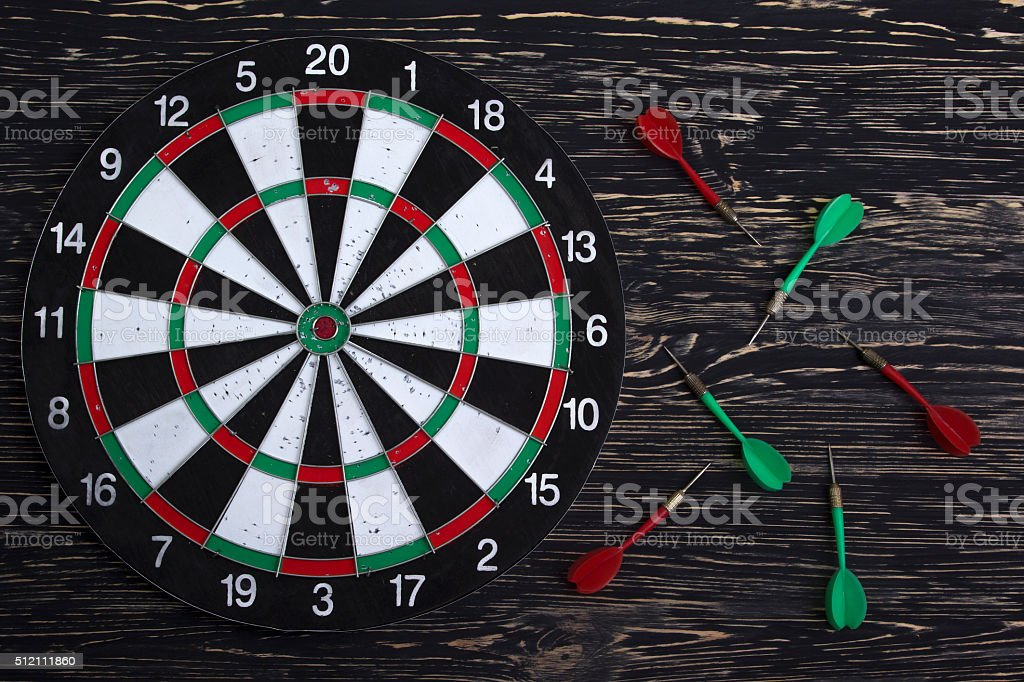 The darts isolated on wooden background stock photo