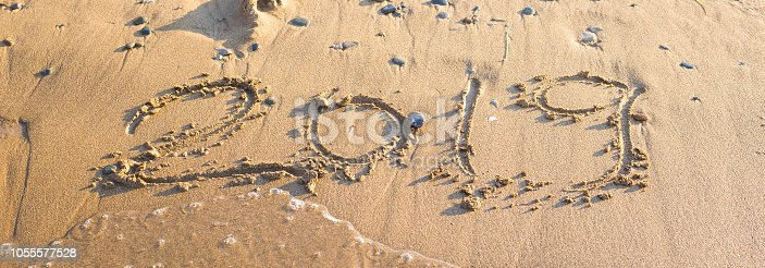 istock 2019 - the date of the new year is written on the yellow sand by the sea or ocean. The concept of the New Year holidays and the onset of the new year twenty nineteen. Background 1055577528