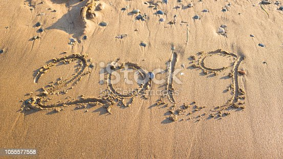 istock 2019 - the date of the new year is written on the yellow sand by the sea or ocean. The concept of the New Year holidays and the onset of the new year twenty nineteen. Background 1055577558