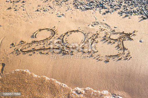 istock 2019 - the date of the new year is written on the yellow sand by the sea or ocean. The concept of the New Year holidays and the onset of the new year twenty nineteen. Background 1055577594